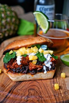 This Pineapple Guajillo Chile Pulled Pork is slow simmered in pineapple juice, Mexican oregano and a blending of guajillo peppers, and habanero. Cooked to tender, shredded goodness it is layered atop mashed black beans, Mexican Crema, diced pineapple and cilantro all on a toasted ciabatta roll.