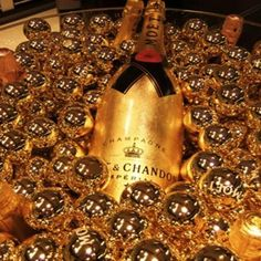 Photo backdrop:: find a giant Magnum of Champagne (empty best) and put in a giant bowl or bucket with gold balls. Guests can grab bottle and use as prop