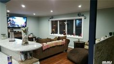 the view from the kitchen to this open floor plan, cozy living space at 141-43 South Dr. Malba NY