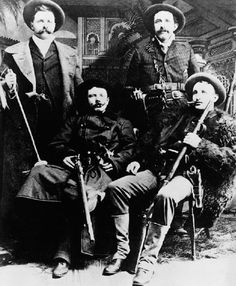 Cole and Bob Younger standing behind Frank and Jesse James