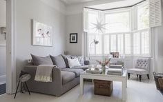 Victorian terrace sitting room, plantation shutters, white wooden floors, grey sofa, light grey walls: