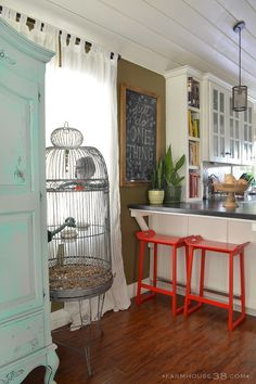 Eclectic and colorful home - love the giant bird cage and red bar stools eclecticallyvintage.com