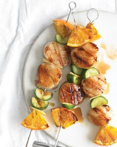 Thread scallops, orange wedges, Kirby cucumber, and thin slices of fresh ginger onto skewers and baste with honey and orange juice. These colorful seafood kebabs can be cooked on the grill or under the broiler.