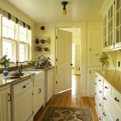 love this simple cottage galley kitchen, creamy and comfy and warm, nice details...and not over-the-top expensive.