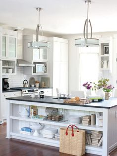 This kitchen has glazed cabinet doors on either side of the hood, along with a nice black countertop.  I don't like the pendants or the open shelving.