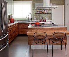 No projeto da designer de interiores Magda Marconi, tanto os armários quanto a ilha são de madeira de demolição. A cor no ambiente fica por conta das pastilhas de vidro que revestem as paredes