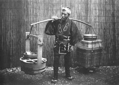 Laborer bearing burdens on pole. Old Japan