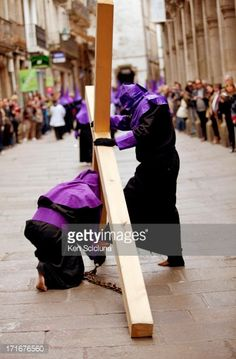 Foto de stock : Santiago de Compostela, Galicia, Northern Spain, Bare foot Nazareners  carrying metal chains and cross during Semana Santa processions as a penitence