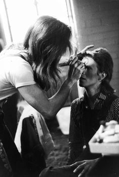 Make-up artist Pierre La Roche prepares English singer David Bowie for a performance as Aladdin Sane, 1973.
