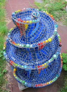 The Mosaic Marble Run is constructed over three large plant pots glued one on top of the other and then covered in ferrocement and mosaics