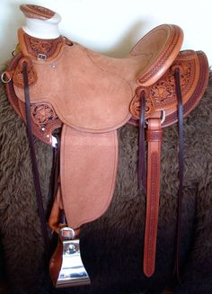 A punchy medium weight (around 35lbs) Inskirt Wade saddle, built on a 94 degree bar that fits a well built muscular shoulder horses.  Seat is finished at 15 &1/4 inch with a close contact deep pocket fit.  Gullet is 7 & 1/2 inch height by 6 & 1/2 width with the back hand hole width at 4 inch.  Horn - 3 inch height by 4 inch width Guadalajara.  Cantle is 4 inch in height by 12 & 1/2 in width with a Cheyenne roll.  In skirt riggin at 7/8ths.  Stainless Steel Stirrups are 5 inch, leather lined…