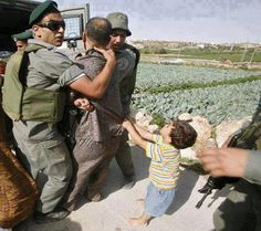 A Palestinian child is trying to save his father from being arrested by some Israeli soldiers, using just his little hands to grab him.  This is just heartbreaking!