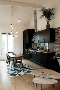 Black kitchen, loft features. Lovely inlaid tile in the hardwood floor defines table area, as do the seven staggered pendant bulbs. pinterest: extromil ♛