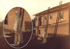 Taken in 1977 in Kramer, Pennsylvania, the picture appears to have captured a strange costumed woman in white as she slowly walks by the house. The photographer was surprised to see this figure on film as no one other than the workmen pictured had been present at the time the photograph was taken.