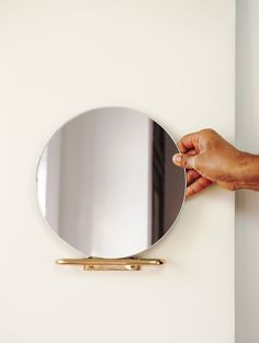 A simple wall mirror with a brass loop bracket that attaches to the wall and becomes the support for a small modern mirror.