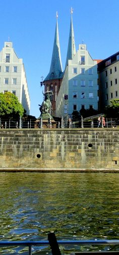 View of St. Nicolas Church, the oldest church in Berlin - it was mainly destryed in WWII and has been restored, and Centaur Statue on River Spree - Berlin, Germany,
