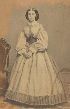 The woman in this photo is wearing a Swiss Belt. This belt was cut wide with a triangular piece in front. This was a popular accessory of the Crinoline era.