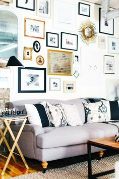 White gallery wall, acrylic side table with gold legs, light grey couch with patterned pillows, black and white patterned rug, wood floors, and a wood coffee table