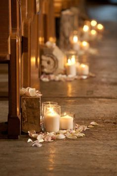 Ceremony decor: A couple cylinders with a taller candle and some fresh petals on the floor surrounding.