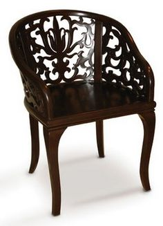 The Damask Arm Chair presents a remarkable feat of traditional craftsmanship featuring an exquisitely hand carved damask pattern in a curved back; shown in solid maple with a dark rosewood stain.