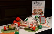 Pittsburgh-based Common Plea Catering packs lunches in clear 18-inch mailing tubes from U-Line. Using red and green ends to indicate the kind of sandwich inside the tube (green for vegetarian and red for meat), the catering team packs every tube with a can of soda or water, whole fruit, wrap, dessert, and small can of Pringles potato chips. Cost: approximately $17 per person.