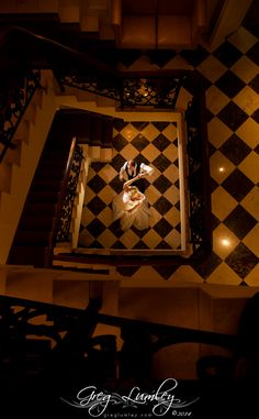 Bride and groom dancing in stairway entrance hall.  Wedding photos taken at night.  Night shoot by wedding photographer Greg Lumley.
