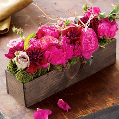 In a different color. // A bouquet of fuchsia peonies, sweetheart pink garden tea roses, burgundy dahlias, antiqued mauve roses and natural branches surrounded by lush mosses is expertly arranged in a hand crafted wood box.