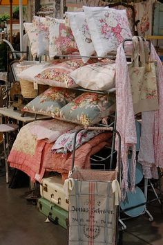 Love the combination of vintage look textiles with old suitcases and metal racks.