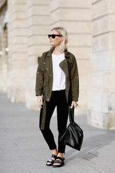 Army Green Anorak Jacket. Crisp White T Shirt. Black Denim Jeans. Studded Sandals. Classic Black Sunglasses. Woven Bucket Leather Bag.