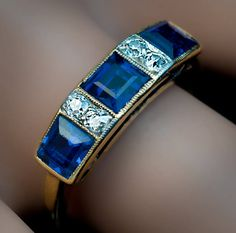 Antique Edwardian Sapphire Diamond 18K Gold Ring, Circa 1910. A stylish 18K gold ring is set with three step-cut sapphires separated by two pairs of old single cut diamonds in a milgrain setting.