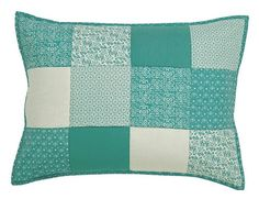 This sham features a patchwork block pattern with vintage prints and solids in blue-green and off-white with a green-blue print border. https://www.uptowncasual.com/products/sea-glass-quilted-standard-sham-21x27 #uptownquiltedbedding