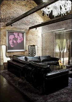 Lenny Kravitz's New Orleans living room with embossed sofa and an oversized print of Billie Holiday. Sitting in front of the Holiday print against the exposed brick wall are 2 incredible wingback chairs. Those chairs would look great in my living area!