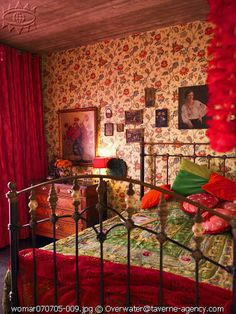 love the bed covers and the huge pile of pillows and cushions piled up. Also the arrangement of pictures on the patterned paper behind the bed.