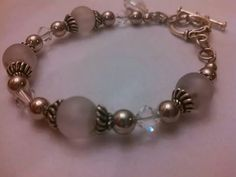 Smokey larger glass beads and crystals with metal round spacers with toggle clasp and crystal charm dangle.   $15.