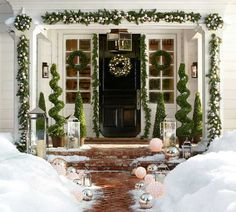 I absolutely love how they've decorated the opening of this porch. Note the wreaths at each corner instead of making the garland one continuous strand. I also love the topiaries between the trees, the large & small lanterns and the silver and lit balls lining the walkway.