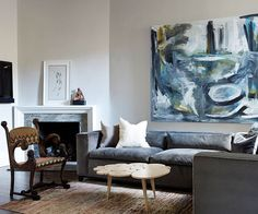 This monochromatic living room gathers inspiration from an oversize painting hung low above the gray sofa. Other art pieces and sculptural furnishings -- such as the unique coffee table -- complement the graphic nature of the large painting. Simple Living Room Decor, Eclectic Living Room, Formal Living Rooms, Monochromatic Living Room, Contemporary Living Room Furniture, Modern Furniture, Furniture Design, Victorian Chair, Unique Coffee Table