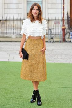 Alexa Chung in a gold skirt and lace ruffle top from the Chanel Paris-Dallas collection.