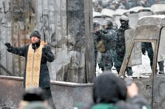Orthodox priest trying to prevent a clash between demonstrators and the police in Kiev, Ukraine - Imgur