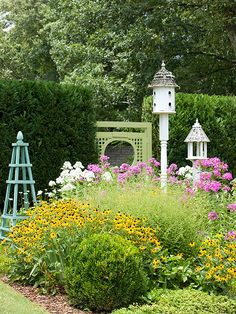 Even a small garden can become a haven for birds and butterflies when you choose flowers they prefer. For example, this square bed is packed with bird and butterfly favorites, such as black-eyed Susan and phlox. A bird feeder and birdhouse add to the garden's wildlife-friendly features.