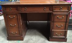 SLIGH-LOWRY WOOD DESK WITH A BEAUTIFUL BROWN LEATHER INLAID TOP AND GOLD-COLORED TRIM. IT HAS 8 DOVETAILED DRAWERS AND BRASS HARDWARE. IT DOES HAVE SOME SCRATCHES ON THE INTERIOR WHERE A CHAIR MIGHT HAVE BRUSHED AGAINST IT, BUT OTHERWISE IT IS IN GOOD CONDITION. MEASURES 30 IN. H X 48 IN. W X 23 IN. D.