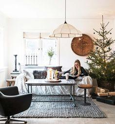 Vardagsrummet är inrett med en mix av saker och möbler från olika tidsepoker. Ljusstake och julgransbelysning med höga ljus från Konstsmide. Bordet består av en underdel som hittades på en skrot och en marmorskiva köpt på loppis. Taklampan från 1920-talet är ett loppisfynd liksom dekorationen på väggen. Matta från en numera nedlagd affär.