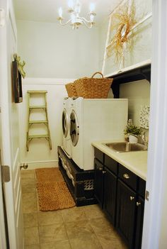 Space under washer/dryer functioning to both lift appliances up and be a storage area for laundry baskets.
