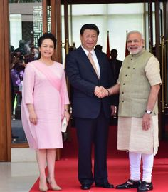 Earlier in the day, when she landed in Ahmedabad, China's First Lady wore a pretty pink dress, popularized by Audrey Hepburn and Jacqueline Kennedy. The kneelength dress had a flowy scarf stitched to one side. She accessorized her look with a white clutch, cream pearl studs and beige suede heels.