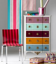 Renew damaged surface with coats of bright colorful paint! Sometimes its easy to just sand and paint a dresser to match a chosen theme, like striped here.