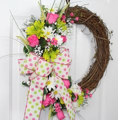 * Part of our Budget Friendly Collection  This cheerful Grapevine wreath has a cheery bow of white with pink and lime polka dots and pink edging.  A delightful combination of pink roses, lime Shasta daisies, and white daisies. Faux babies breath, pink small flowers and grasses give this wreath a look that will last on your door from spring through summer! Great for inside walls and doors, as well as a front door welcome.  Back of wreath has patches of mossing to protect your doors or walls…