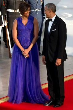 Michelle Obama with her husband, President Barack Obama, in an electric purple Tadashi Shoji gown.