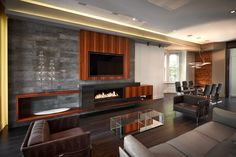 This modern living room has a long rectangular fireplace built into the entertainment center. The television takes the spotlight in this room, but the fireplace sets a warm and inviting atmosphere.