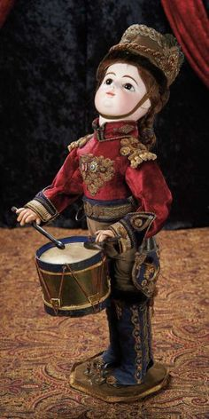 """French Bisque Automaton """"The Drummer Boy"""" in Regimental Costume -The figure is wearing velvet regimental costume with elaborate insignia and trim, matching helmet, and carries wooden drumsticks in his hands. When wound, he vigorously beats the drum. Marks: F. 10 G. Comments: French, circa 1882."""