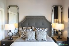 Upholstered headboard with tall mirrors over nightstands
