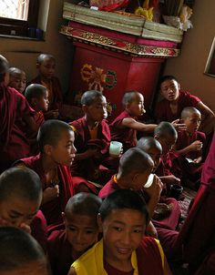 Little monks drink tea with dharma muffins, at a break in the side room, during Sakya Lamdre, Tharlam Monastery of Tibetan Buddhism, Boudha, Kathmandu, Nepal